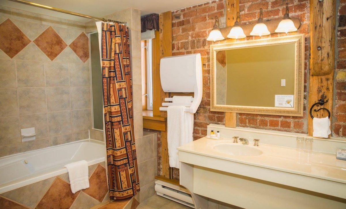 Queen Bathroom with towel warmer and exposed brick wall.