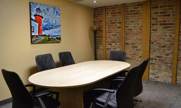 Boardroom with boardtable that seats 6, exposed brick wall and tall lamp in the corner